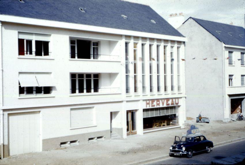 L'immeuble, typique de la reconstruction de Saint-Nazaire date de 1954. Il a abrité le magasin et les ateliers Herveau jusqu'en 1984.