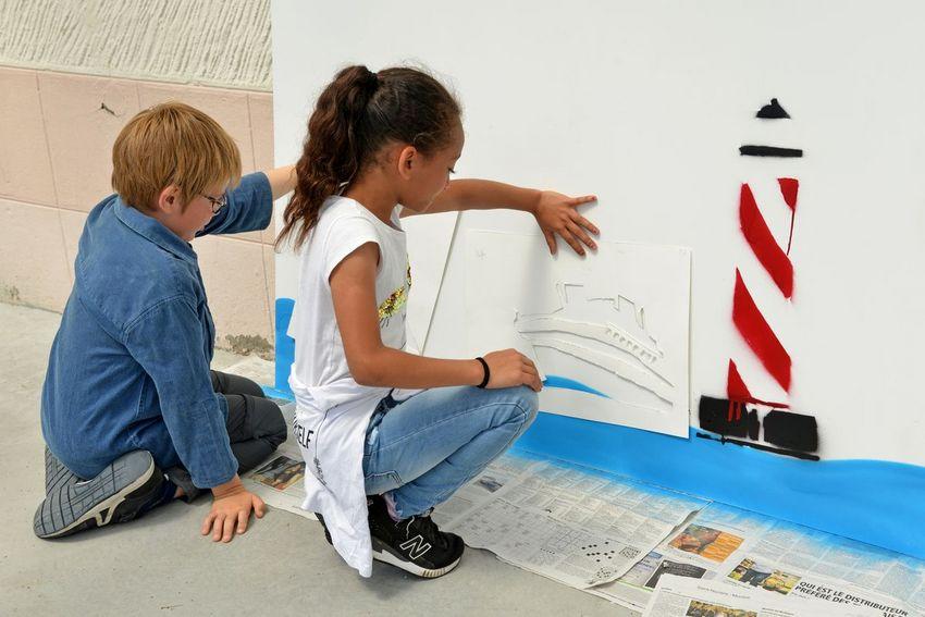 Les enfants de CP sont concentrés sur leurs pochoirs lors d'un atelier avec le street artist Jinks Kunst. (©Ville de Saint-Nazaire - Christian Robert)