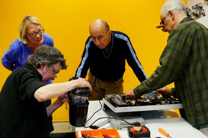 Trois habitants de Saint-Nazaire viennent réparer des objets avec l'aide de Michel. (©Ville de Saint-Nazaire - Blandine Bouillon)