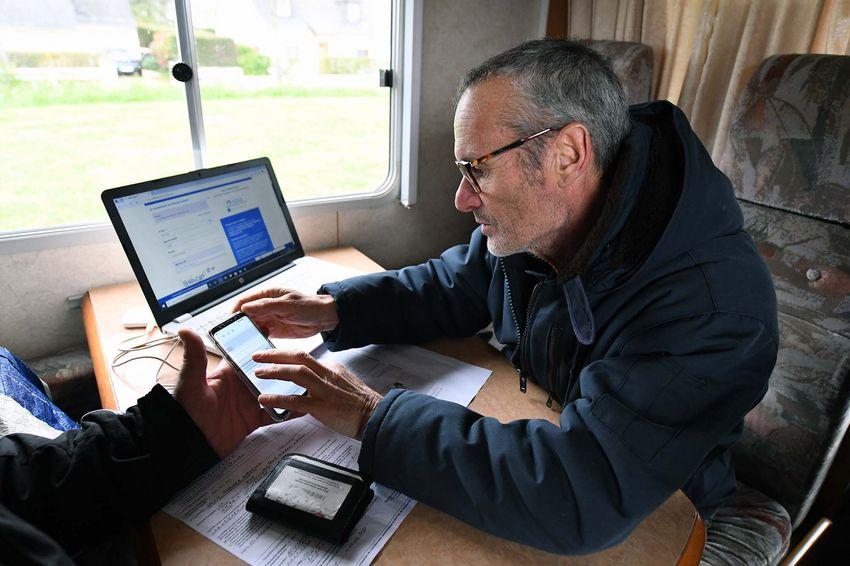 Patrice, bénévole, aide un Nazairien dans ses démarches en ligne. (©Ville de Saint-Nazaire - Christian Robert)
