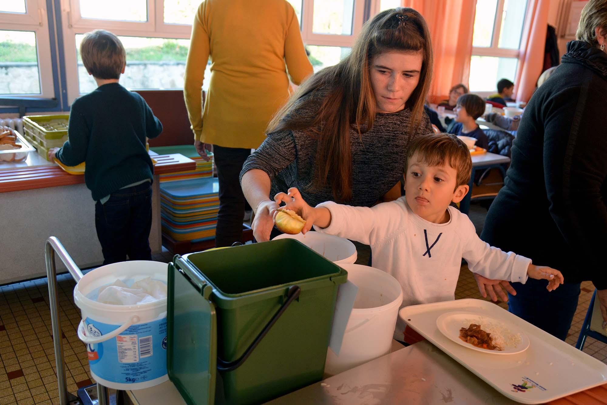 Avec Kelly, Enzo jette le reste de sa pomme dans le bac dédié au compost. (©Ville de Saint-Nazaire - Christian Robert)